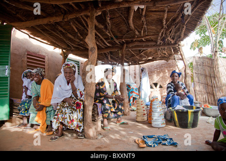 In northern Burkina Faso, a Fulani wedding has taken place. Women bring gifts-pots, textiles, etc-to the bride's - Stock Photo