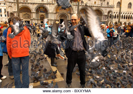 Tourists feeding pigeons in St Marks Square - Venice Italy - Stock Photo