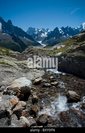 A river leads from Lac Blanc, opposite the peaks of Aiguille Verte and Mont Blanc, French Alps. - Stock Photo