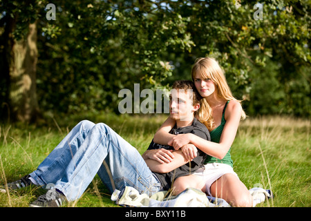 A young couple sitting in a park, woman embracing her boyfriend - Stock Photo