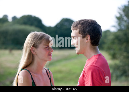A young couple standing outdoors, smiling at each other - Stock Photo