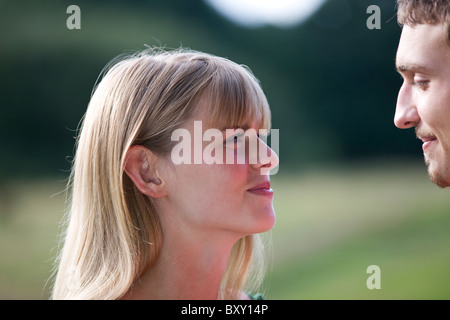 A young couple outdoors, smiling at each other - Stock Photo