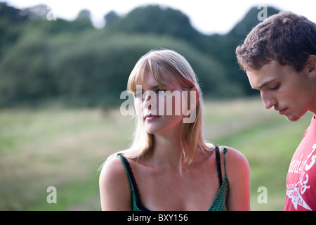 A young couple outdoors, looking thoughtful - Stock Photo