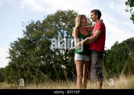 A young couple standing outdoors, embracing - Stock Photo