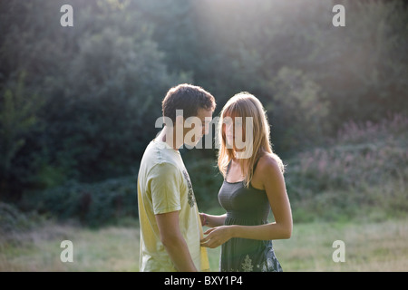A young couple standing outdoors, man looking thoughtful - Stock Photo