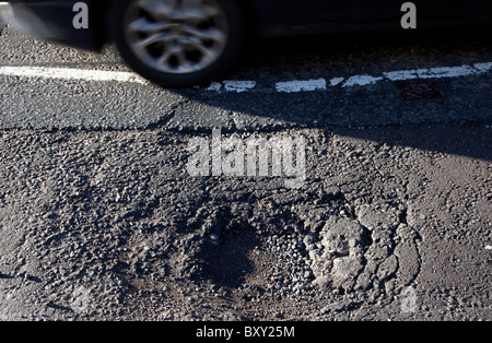 Pothole in London street after severe winter weather - Stock Photo