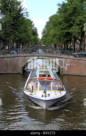 Bridge and tourist boat on the canal at Leidse Gracht in Amsterdam, Holland - Stock Photo