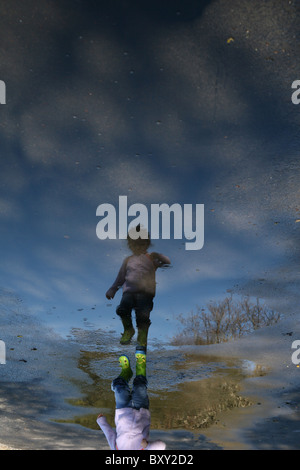 A young child walking through a puddle full of cloud reflections. - Stock Photo