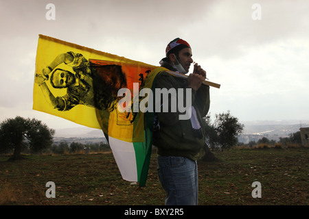 Palestinian man walking with a flag bearing the image of Marwan Barghouti a Palestinian political figure imprisoned - Stock Photo