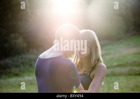 A romantic young couple outdoors in the evening sun - Stock Photo