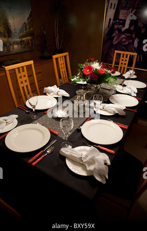 Table setting on a black tablecloth with a floral arrangement and pictures on the wall of the dining room. - Stock Photo
