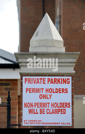A car clamping company notice in a private car park for residential apartments UK - Stock Photo