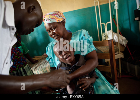 A child receives an injection at Amuria Health Centre IV - Amuria District, Uganda, East Africa. - Stock Photo