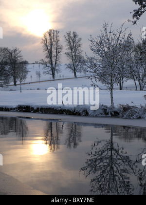 View of a partly frozen Grand Union Canal in the foreground with sun setting in the background - Stock Photo