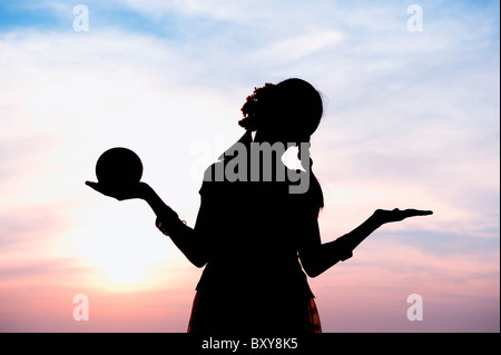 Indian girl silhouette balancing a round shape in her hand in an unconcerned carefree pose. India - Stock Photo