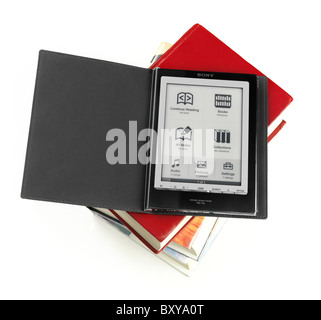 Sony Reader electronic book reader on a pile of hard cover books. PRS-700 Portable Reader System. Isolated on white - Stock Photo