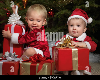 Two year old girl and an eight month old boy opening their gifts under a Christmas tree - Stock Photo