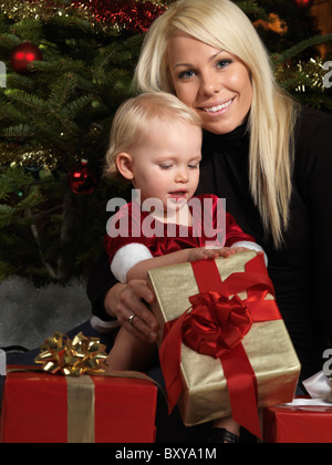 Portrait of a mother and her daughter opening presents under a Christmas tree - Stock Photo