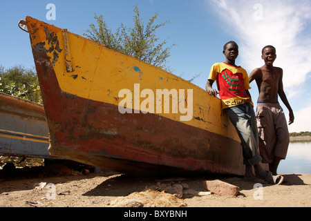 Two boys by the fishing boats on Nile river bank in Abri, Sudan - Stock Photo