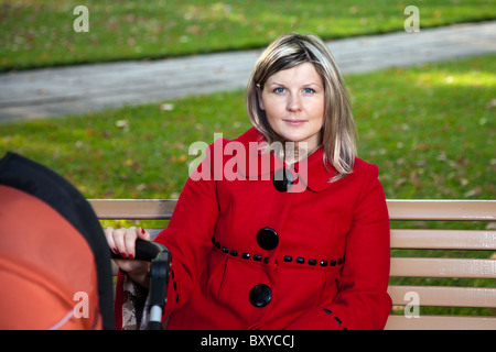 Blond woman in red coat holding handle or pram. - Stock Photo