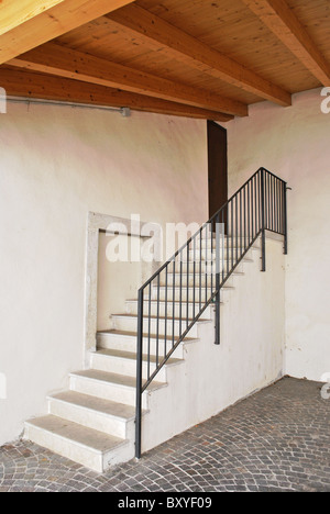 white cement staircase with wooden roof beams and pine - Stock Photo
