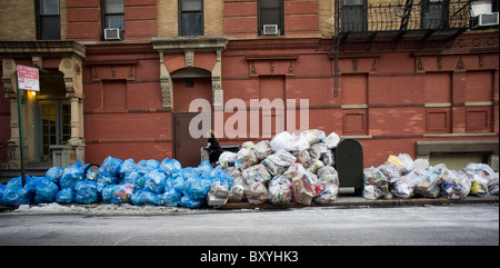 Bags of trash await pick-up in the Chelsea neighborhood of New York - Stock Photo