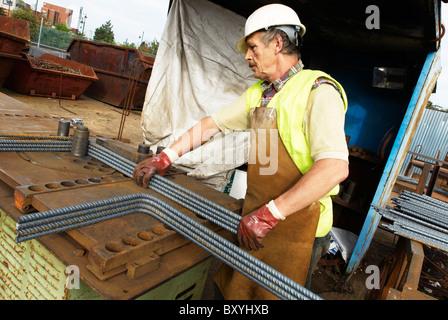 worker bending steel rods concrete reinforcement steel rebar cut and bent factory worker bending steel rods stock rebar worker