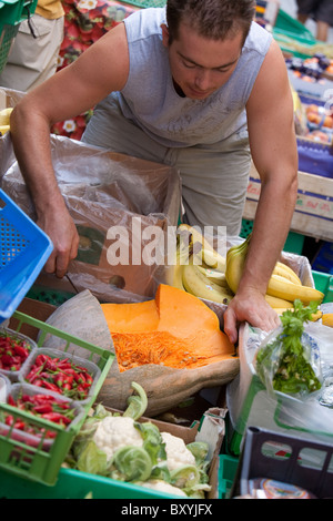 Cutting up fresh portions of melon at greengrocers . Fresh fruit and vegetables for sale on the streets of Valletta - Stock Photo