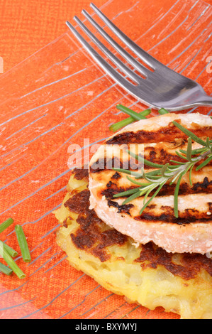Roesti and grilled salmon with chives and rosemary served in a glass dish - Stock Photo