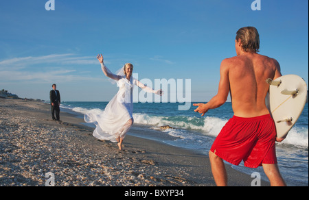 Young bride running into lifeguard's arm on beach - Stock Photo