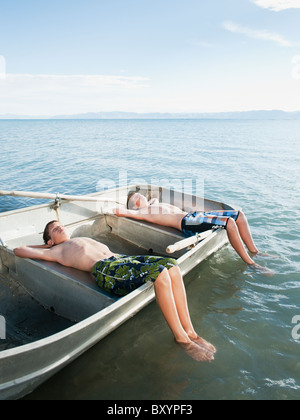 Two Shirtless Boys Lying Side By Side And Looking At