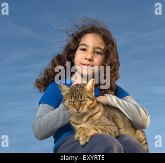 little girl holding a cat against blue sky - Stock Photo