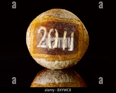 round loaf of bread dusted with the new year date 2011 - Stock Photo