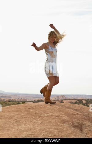 Young woman dancing on rocks - Stock Photo