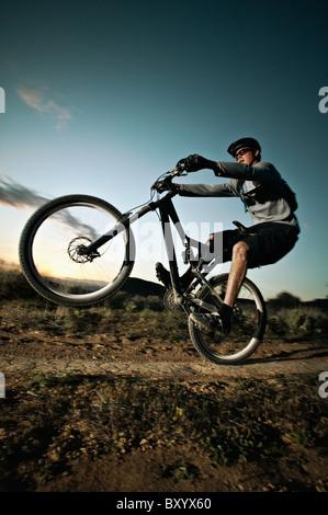 Man mountain biking on dirt track - Stock Photo