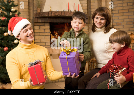 Portrait of joyful children looking at their presents surrounded by parents - Stock Photo