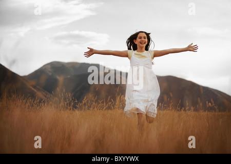 Girl running through wheat field - Stock Photo