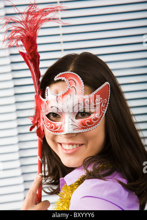 Portrait of beautiful girl wearing carnival mask and looking at camera - Stock Photo