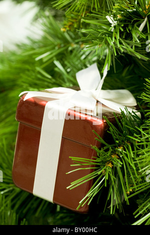 Close-up of red giftbox hanging on fir tree branch as decoration - Stock Photo