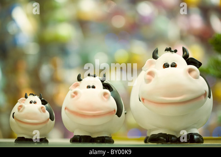 Image of three fat toy cows standing in line on shop window - Stock Photo