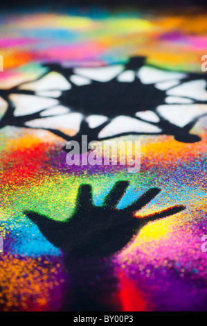 One world unity symbol surrounded by childrens hand prints made with multicoloured powder - Stock Photo