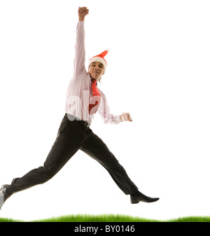 Portrait of excited businessman wearing santa cap in high jump - Stock Photo