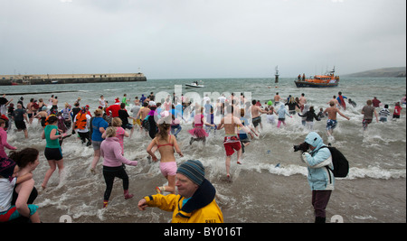 Hundreds of people run into the sea for annual new years day dip at Peel, Isle of Man - Stock Photo