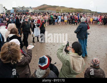 Hundreds of people about to run into the sea for annual new years day dip at Peel, Isle of Man - Stock Photo