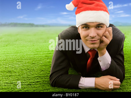 Smart businessman wearing red santa cap having rest on green glade in summer - Stock Photo