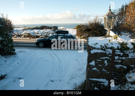 Car on snowy road passing by a driveway - Stock Photo