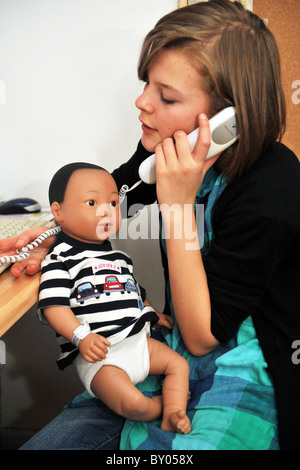 A 13 year old girl minds a 'real care baby' for the weekend as part of a school project to prevent teenage pregnancy - Stock Photo