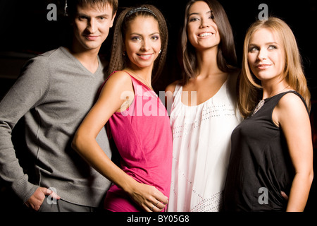 Portrait of happy friends smartly dressed during party in club - Stock Photo