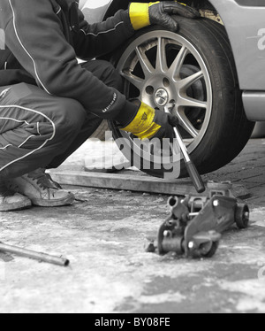 A mechanic unscrewing the wheel nuts with a wrench to remove the wheel from a car, wearing rigger gloves for protection. - Stock Photo