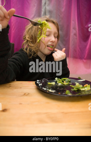 Eleven year old girl playing with her food - Stock Photo